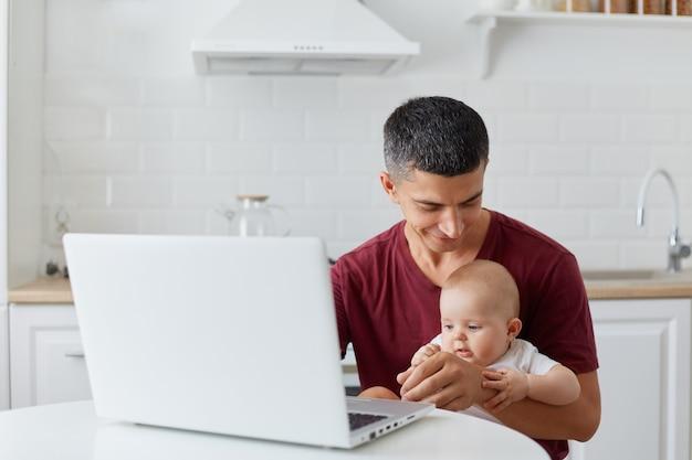 ノートブックの前に小さな娘や息子と一緒に座って、大きな愛を込めて赤ちゃんを見ている、栗色のカジュアルなtシャツを着た若い大人の父親の屋内ショット、子供の世話をしながらフリーランサーの仕事。