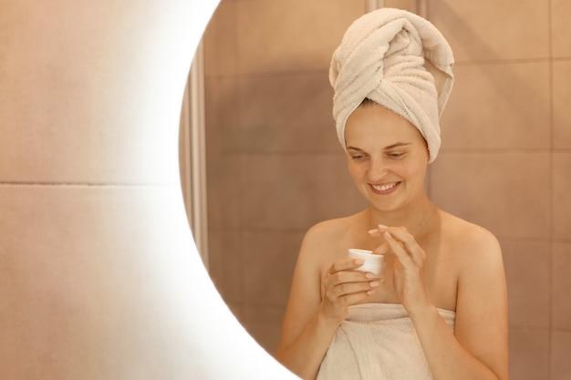 若い大人の女性が肌の世話をし、鏡の前のバスルームで化粧用クリームを手にポーズをとり、裸の肩とタオルを頭に置いて立っている屋内ショット。
