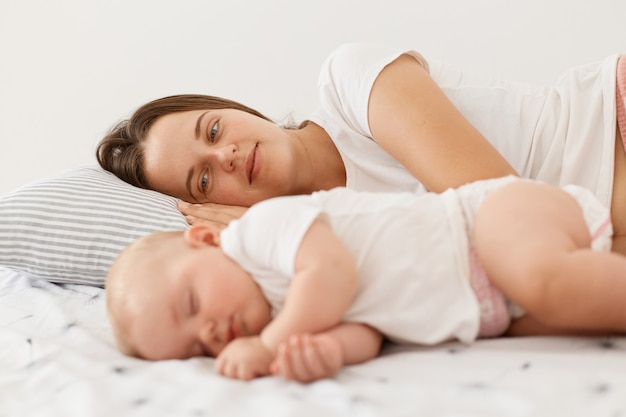 어린 성인 어머니가 잠자는 아기 옆에 누워 큰 사랑으로 작은 딸을 바라보는 실내 사진, 흰색 캐주얼 스타일의 티셔츠를 입은 여성, 아침에 집에서 포즈를 취하는 여성.
