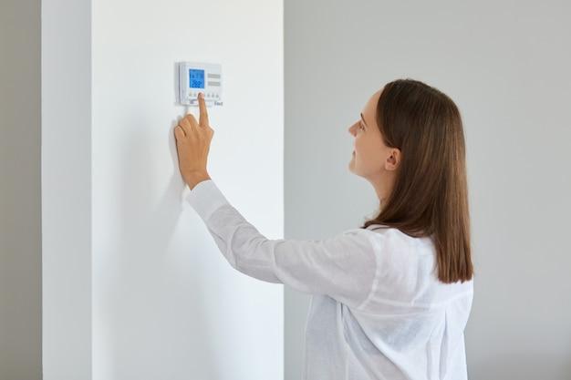집의 흰 벽에 설치된 현대적인 무선 온도 조절기로 난방 온도를 조절하는 젊은 성인 여성의 실내 사진. 스마트 홈 난방 조절.