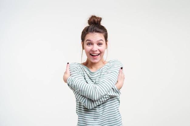 젊은 동요 갈색 머리 여자의 실내 촬영은 흥분하게 그녀의 눈썹을 올리면서 자신을 포용하고 넓게 웃고 흰 벽 위에 절연