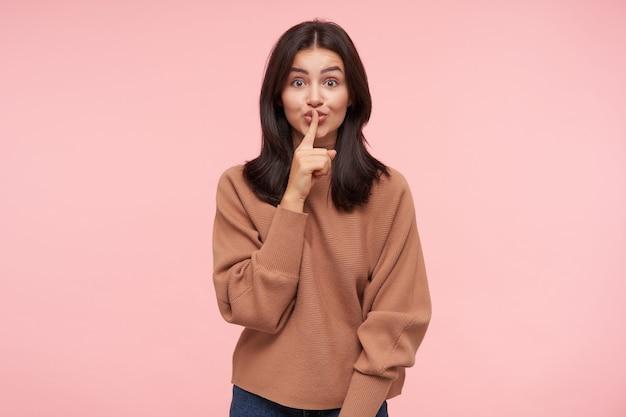 젊은 동요 긴 머리 갈색 머리 아가씨의 실내 촬영, 캐주얼에 분홍색 벽 위에 절연 침묵을 유지하도록 요청하는 동안 자장 제스처로 손을 올리는