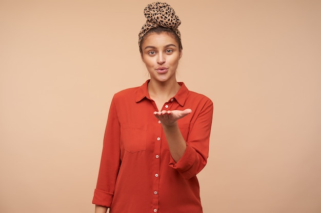 Снимок в помещении молодой привлекательной шатенки, сложившей губы в воздушном поцелуе и положительно смотрящей вперед, стоящей у бежевой стены с поднятой рукой