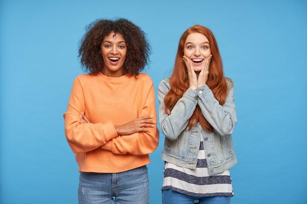 Снимок в помещении молодых привлекательных веселых дам, которые взволнованно смотрят и радостно улыбаются, стоя у синей стены