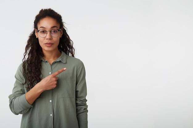 若い魅力的な巻き毛のブルネットの暗い肌の女性の屋内ショットは、白い背景の上に分離された人差し指で脇を指して唇を折りたたんでいます