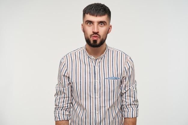 Снимок в помещении: молодой привлекательный темноволосый мужчина с бородой вокруг глаз смотрит со скрещенными губами, держа руки вдоль тела и позирует у белой стены