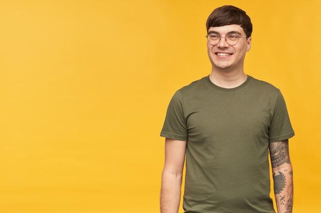 若い魅力的な男性の屋内ショット、丸いスタイリッシュなメガネと緑のtシャツを着て、幸せな表情で広く笑顔