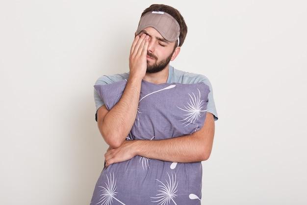 Снимок в помещении молодого привлекательного человека, просыпающегося утром, хочет спать, красивый парень растягивается и зевает, держа свои подушечки
