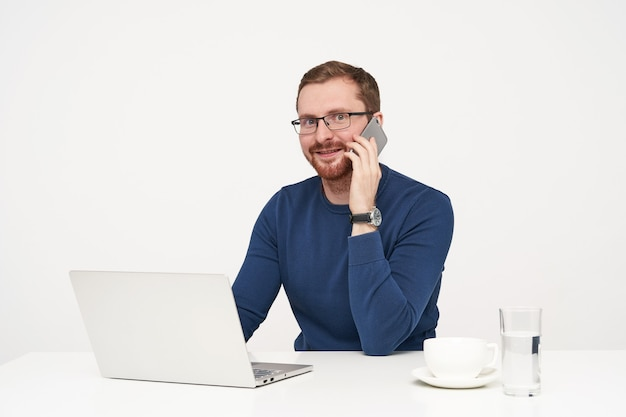 楽しい話をしながら、白い背景で隔離のカメラを驚いて見ながら、携帯電話を上げたまま眼鏡をかけた若いひげを生やした男性の屋内ショット