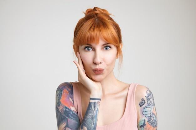 白い背景の上に分離された、カメラを積極的に見ながら彼女の頬に手のひらを保持しているセクシーな髪の若い美しい入れ墨の女性の屋内ショット