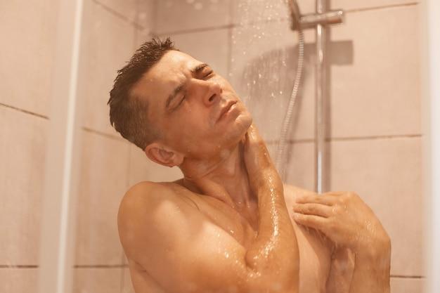 젊은 브루네트 남자가 샤워를 하고 떨어지는 물방울 아래 서서 집에 있는 욕실에서 벗은 몸을 씻는 실내 사진. 남성 바디 케어 및 일상적인 위생 루틴.