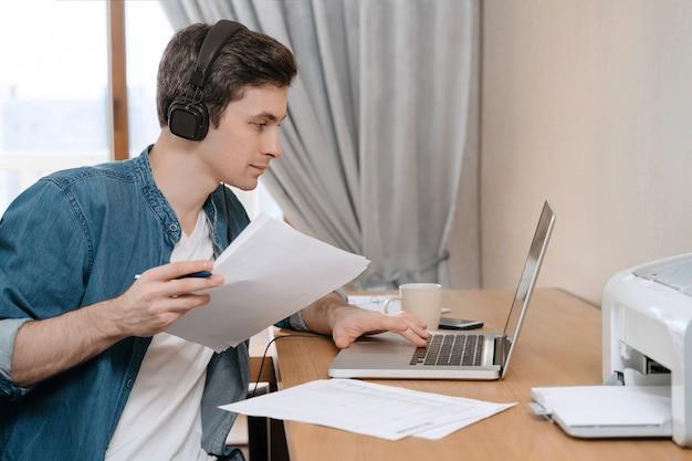 일부 문서를 들고 노트북을 사용하여 그의 책상에서 일하는 젊은 백인 사업가의 실내 샷