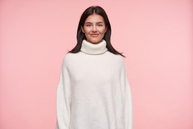 ピンクの壁の上に立って、心地よい笑顔で前向きに前向きに見ている白い腫れたタートルネックに身を包んだ若い魅力的な茶色の髪の女性の屋内ショット