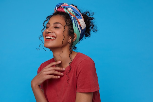Снимок молодой веселой темноволосой женщины в помещении, держащей поднятой рукой на груди и радостно смеющейся с закрытыми глазами, изолированной на синей стене