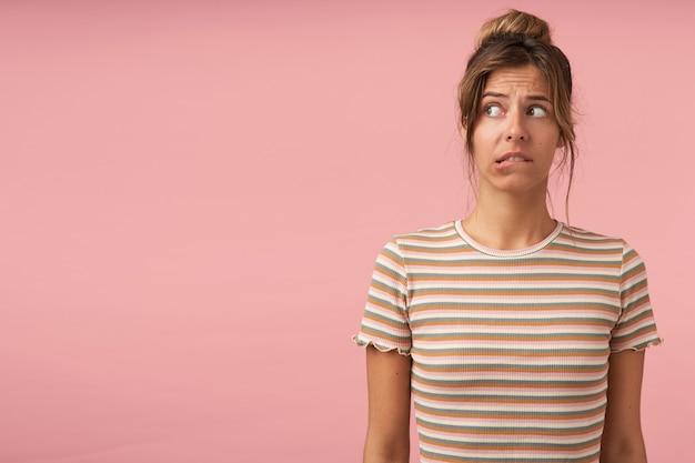 캐주얼 옷에 분홍색 배경 위에 서있는 동안 혼란스럽게 옆으로보고있는 동안 worringly underlip을 물고 젊은 혼란스러운 갈색 머리 여성의 실내 샷