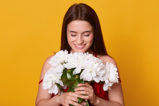 優しい牡丹を手に持って、彼女のブーケを見下ろして、白い花の臭いがする若いかわいい女性の屋内撮影