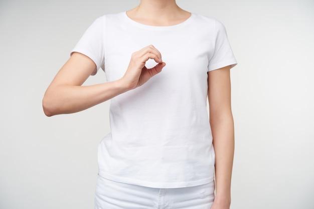 흰색 배경 위에 절연 표시 및 손가락 번호 0으로 가리키는 동안 젊은 공정한 피부를 가진 여자의 실내 촬영은 자신 앞에서 손을 들고