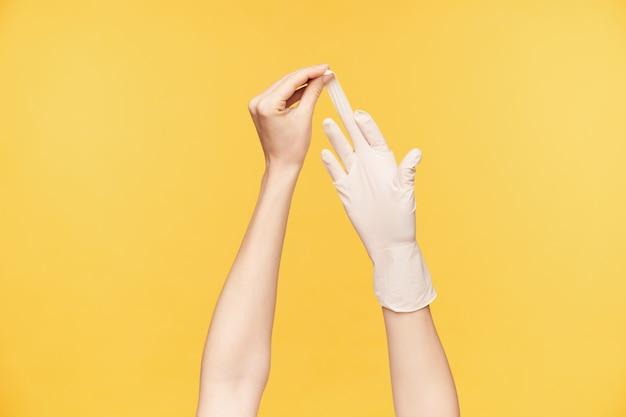 Крытый снимок руки молодой светлокожей женщины, потянувшей белую перчатку из другой руки со средним пальцем, изолированной на оранжевом фоне. концепция человеческих рук