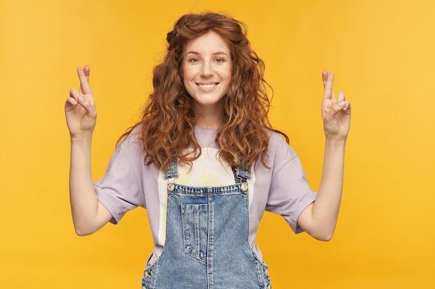 若い女子学生の屋内ショットは、青いデニムのオーバーオールと紫色のtシャツを着て、祈りの姿勢で指を交差させ、良い試験結果を待っています。黄色の壁に隔離