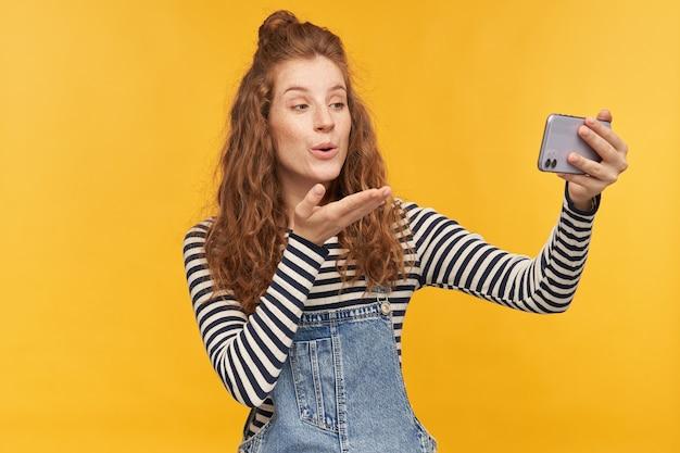 彼女のボーイフレンドと電話で話している若い女性の屋内ショットは、黄色の壁に隔離されたエアキスを送信して、満足と幸せを感じています