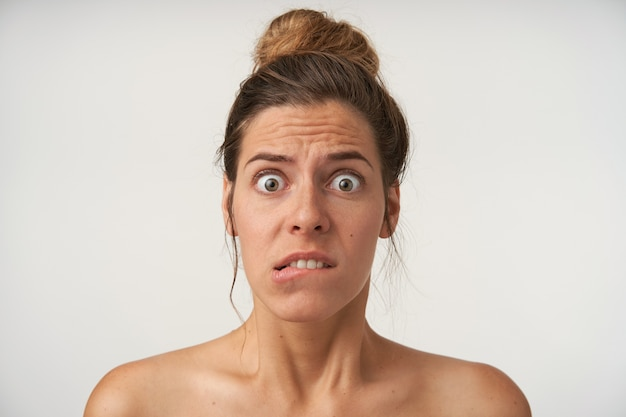 お団子の髪型、しわのある額と噛む下唇、目を大きく開いて見ている若いおびえた女性の屋内ショット