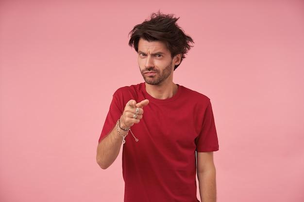 人差し指で指している野生の髪、真面目な顔で立って眉をひそめている、赤いtシャツを着ている若いハンサムなひげを生やした男性の屋内ショット