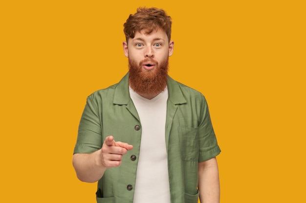 大きなあごひげを生やした若いハンサムな赤毛の男の屋内ショット、ショックを受けた、驚いた表情で正面を直接見て、指で指しています