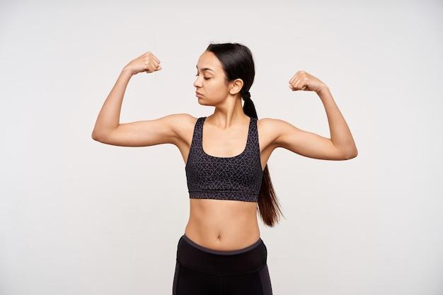 Снимок молодой длинноволосой спортивной брюнетки в помещении, которая внимательно смотрит на свою поднятую руку, стоя над белой стеной в черном топе и леггинсах
