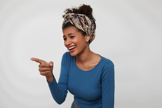色の服で白い背景の上に立って、上げられた人差し指で前を指して幸せに笑っている若い素敵な巻き毛のブルネットの女性の屋内ショット