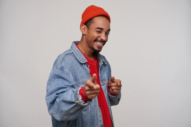 陽気な笑顔でウインク、赤い帽子、プルオーバー、青いジーンズのコートを上げた手で白い壁に身に着けている若い素敵な暗い肌のひげを生やしたブルネットの男の屋内ショット