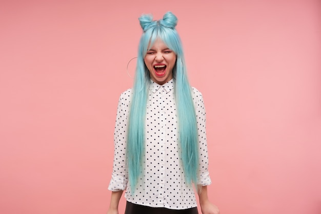 Снимок в помещении молодой милой девушки с синими волосами в стиле аниме, которая держит глаза закрытыми, громко кричит, с прической в виде пучков, стоя с опущенными руками