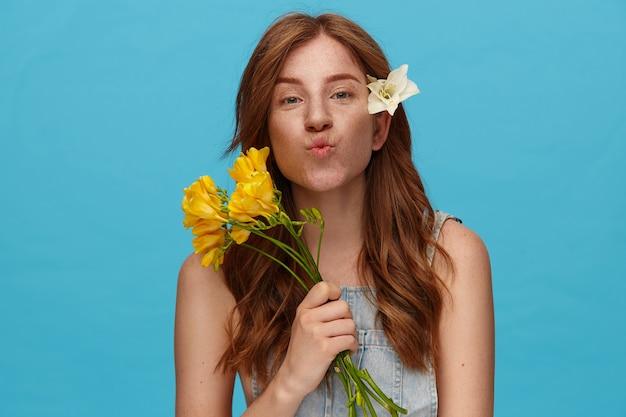 ジーンズトップの青い背景の上に立って、カメラを積極的に見ながら唇を折りたたむ黄色い花を持つ若い素敵な緑色の目の赤毛の女性の屋内ショット