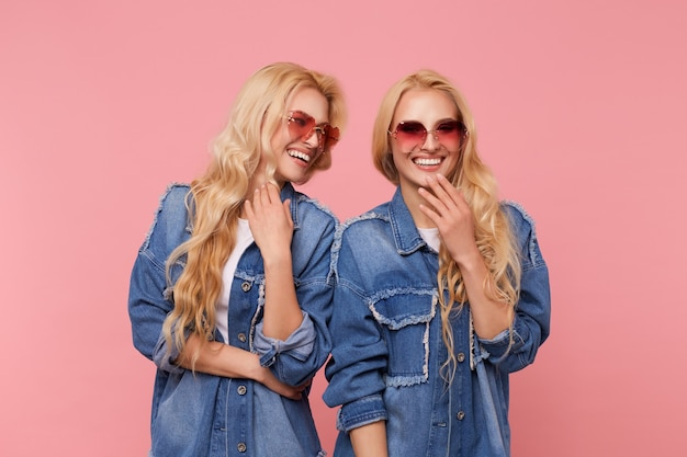 一緒に楽しい時間を過ごし、ピンクの背景の上に立って幸せに笑っている同じ服を着た若い素敵な幸せな長い髪のブロンドの双子の屋内ショット