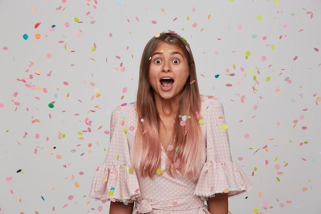 Снимок молодой красивой удивленной длинноволосой женщины, изумленно смотрящей в помещении над белой стеной и красочным конфетти, одетой в праздничную одежду