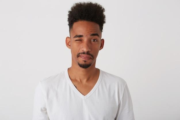 한쪽 눈을 감고 어두운 피부를 가진 젊은 긍정적 인 매력적인 갈색 머리 수염 난 남자의 실내 촬영