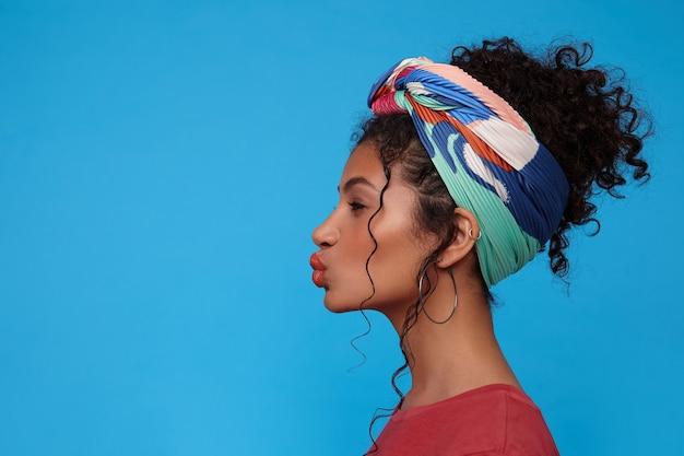 Снимок в помещении молодой позитивной темноволосой кудрявой женщины с непринужденной прической, прищурившейся и формирующей губы в воздушном поцелуе, изолированной на синей стене