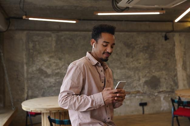 코 워킹 공간을 통해 포즈를 취하는 캐주얼 옷을 입은 젊은 긍정적 인 어두운 피부 수염 난 남성의 실내 촬영, 손에 휴대 전화를 유지하고 밝은 미소로 화면을보고