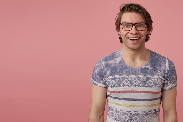 젊은 긍정적인 남성의 실내 사진, 넓은 미소로 카메라를 직접 바라보고, 기쁘고 행복한 느낌