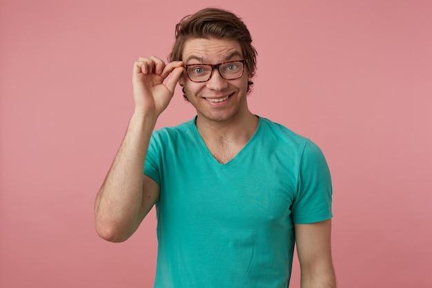 젊은 긍정적인 남성의 실내 사진, 파란색 티셔츠를 입고 안경을 만지고 얼굴에 활짝 웃는 얼굴로 카메라에 직접 충격을 받은 모습