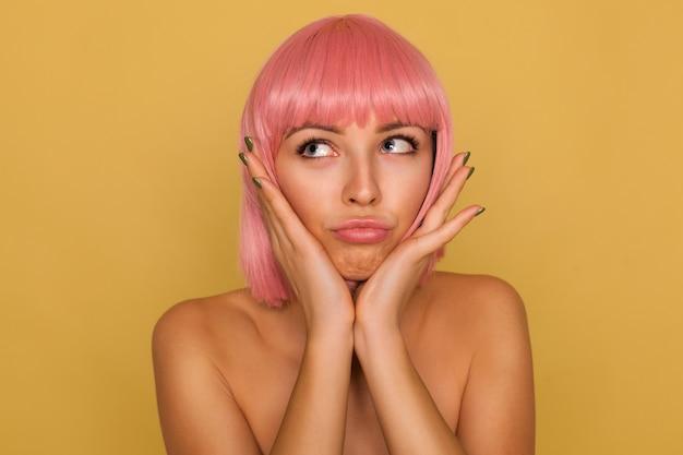 핑크 밥 헤어 스타일이 제기 손바닥으로 그녀의 얼굴을 잡고 의아해 얼굴로 위쪽으로보고, 겨자 벽 위에 포즈를 취하는 젊은 예쁜 파란 눈 아가씨의 실내 촬영