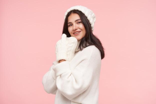 자연 메이크업 접는 젊은 예쁜 갈색 머리 여자의 실내 촬영은 그녀의 얼굴 근처에 손을 제기하고 전면에 긍정적으로 웃고, 분홍색 벽 위에 절연