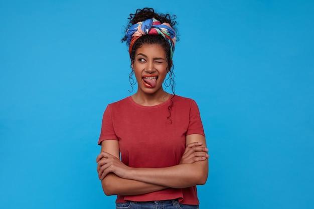 青い壁の上に立って、変な顔をして彼女の舌を見せながら片目でウインクしている若いかなり暗い髪の巻き毛の女性の屋内ショット