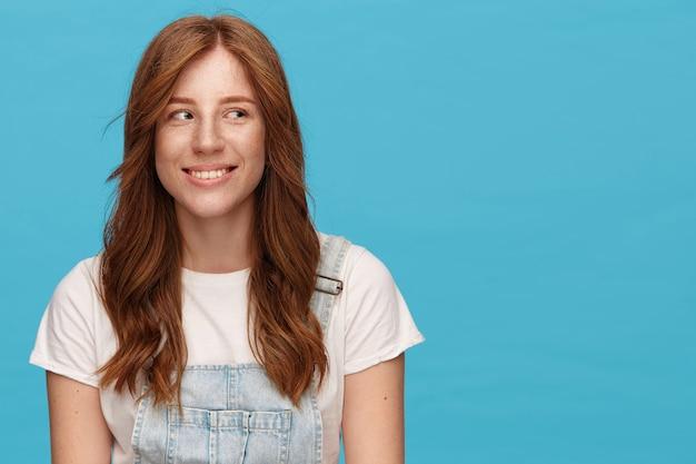 Снимок в помещении молодой красивой рыжеволосой женщины с естественным макияжем, удивительно смотрящей в сторону с приятной улыбкой, одетой в повседневную одежду, стоя на синем фоне
