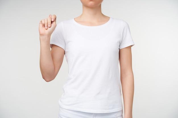 Снимок молодой женщины, держащей поднятой рукой и сжимающей ее, показывая букву t из алфавита смерти, стоящую на белом фоне