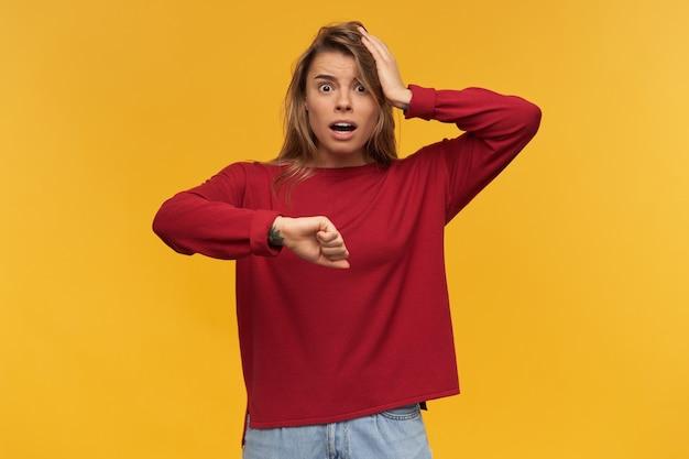 서있는 젊은 여성의 실내 촬영은 혼란스럽고 무서워하는 표정으로 입을 넓게 열어 둡니다.