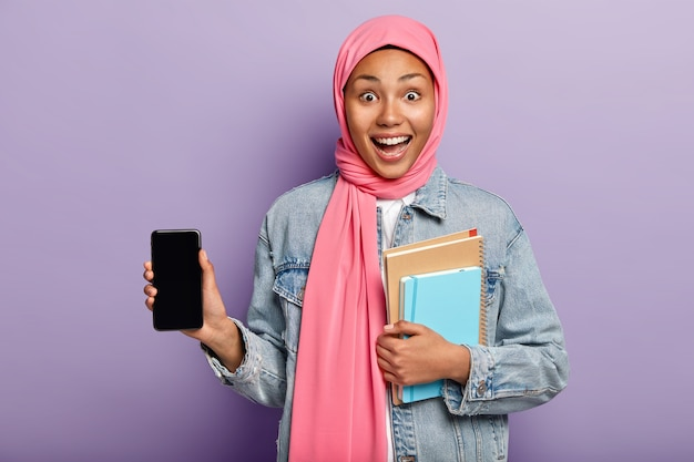 Indoor shot of optimistic dark skinned muslim woman introduces cool gadget