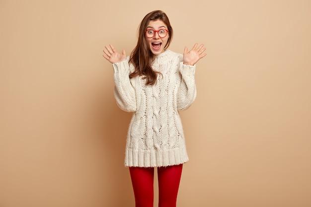 Tiro al coperto di una donna ottimista e soddisfatta esclama positivamente, alza i palmi, ha una reazione sorpresa su qualcosa