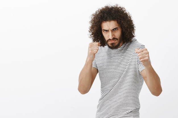 Indoor shot of outraged bully with beard and afro haircut, standing in boxing pose with raised clenched fists, frowning at enemy, being ready to fight
