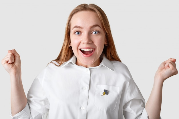 Indoor shot of overjoyed blue eyed young woman with long hair, smiles broadly, being in good mood, rejoices good news, keeps fists clenched, dressed in white shirt, poses indoor. victory concept