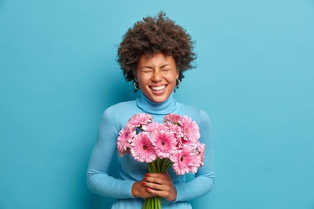 Tiro al coperto di giovane donna dai capelli ricci felicissima ha un'occasione speciale per ricevere un regalo, detiene un bel mazzo di fiori, adora le gerbere rosa